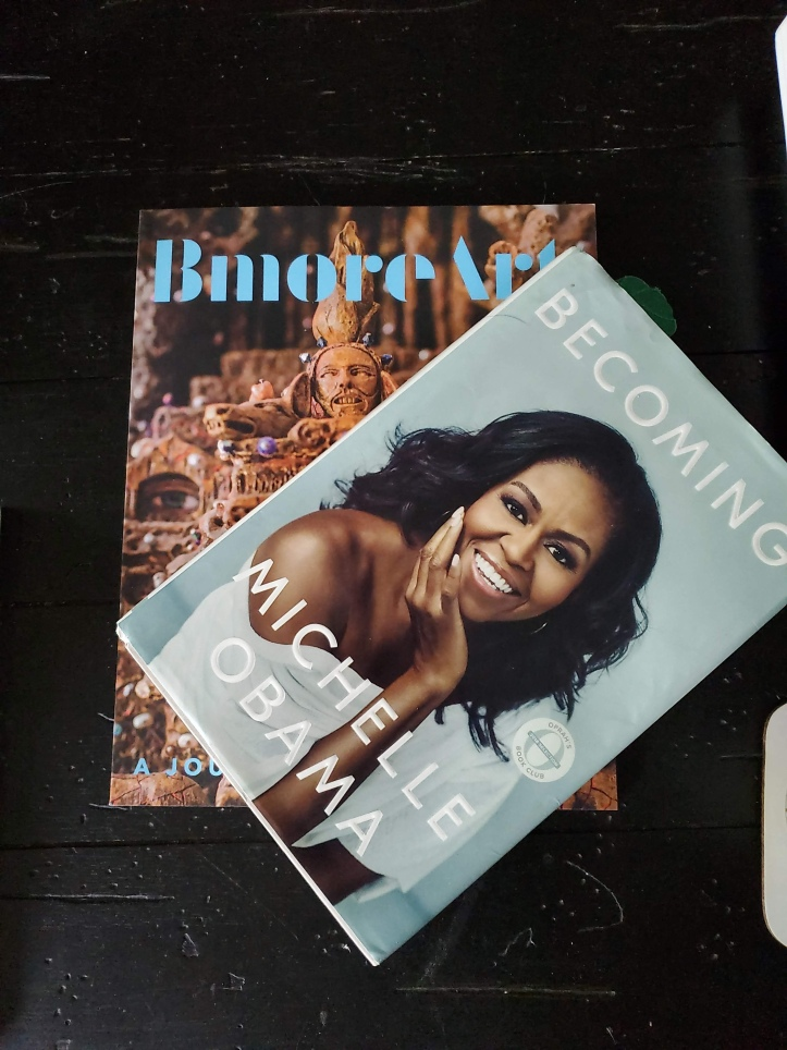 Bmore Art magazine and book Becoming by Michelle Obama on black background