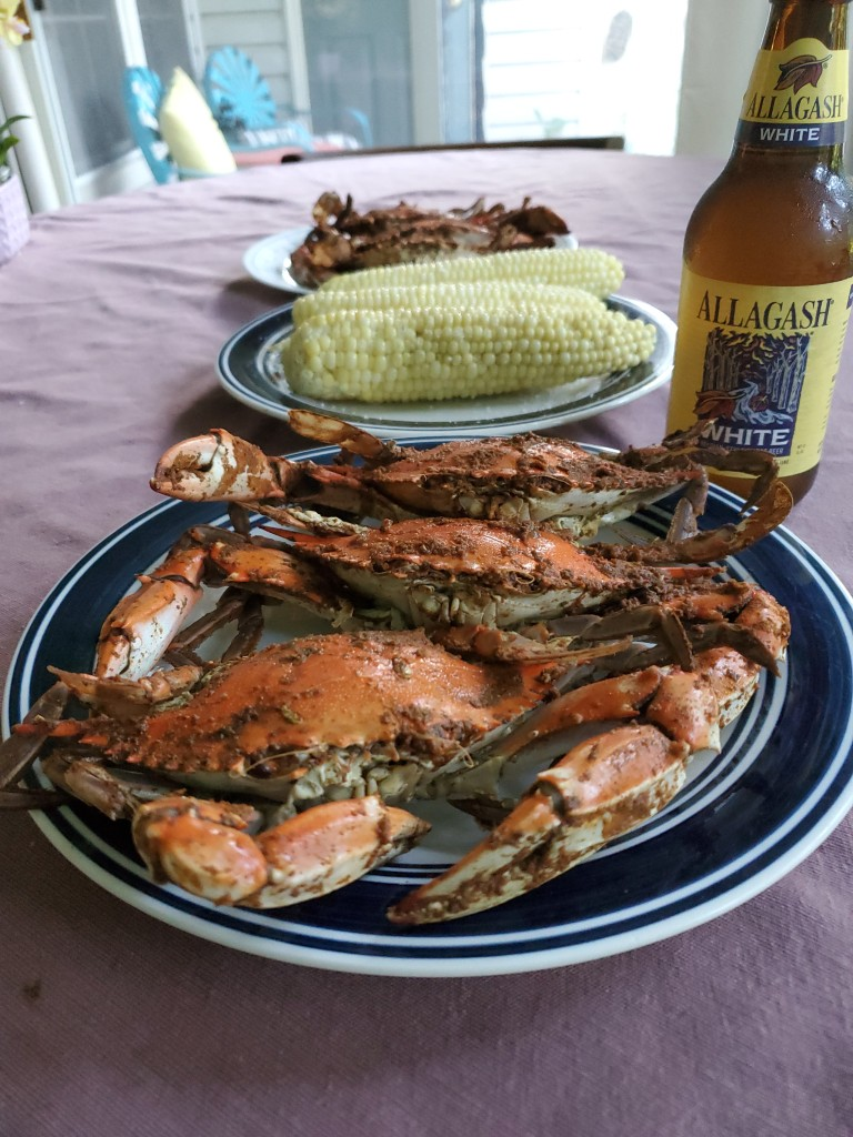 steamed Maryland crabs on blue and white plate, with corn on the cob and an Allagash beer. All on purple tablecloth